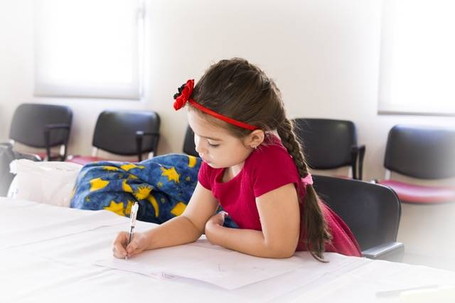 Girl in Red Short Sleeve Dress and Flower Headband Holding Pen and Writing on Paper on Table · Free Stock Photo (55577)